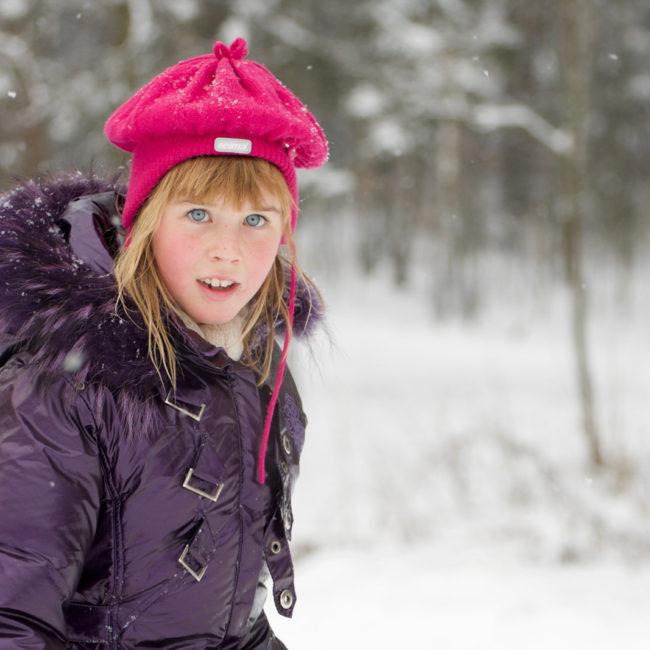 Девочка в розовой шапке в снегу